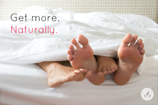man and woman's feet stick out from under the covers, with her leg on top of his.