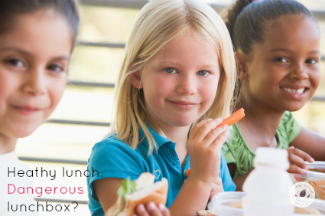 blonde girl surrounded by African American and Latina girls eat lunch happily.