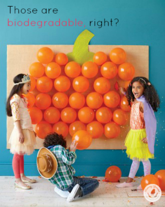 three kids in costumes sticking orange balloons on a blue wall in the form of a pumpkin.