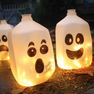 milk jugs with scary faces drawn on them in marker, with lights inside