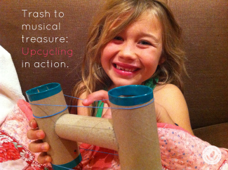 Little girl holding guitar made from upcycled toilet paper rolls and rubber bands.