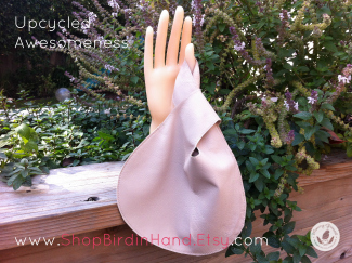 cream leather wristlet bag on mannequin hand against garden background