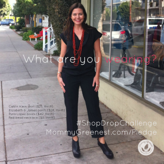 brunette in black pants and shirt with red necklace on city sidewalk