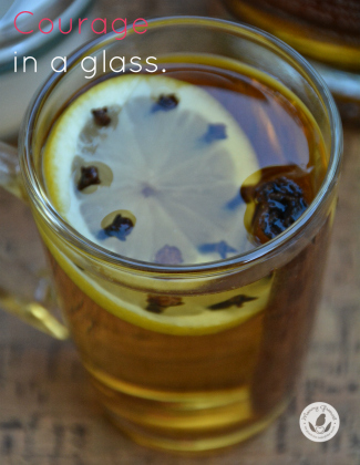 hot toddy in glass with lemon slice and cloves