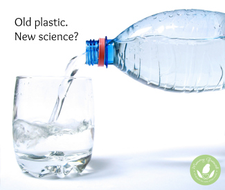 plastic water bottle pours water into a clear glass