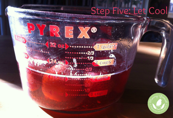 strawberries and water in pyrex measuring cup against wood background