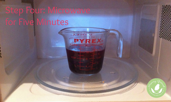 pyrex cup with blueberries and water in microwave