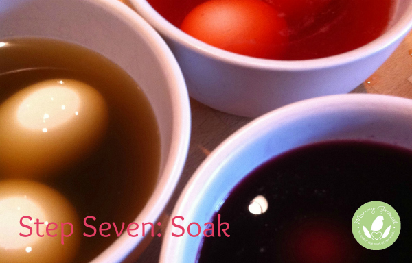 eggs soak in natural easter egg green, purple and red dyes in white bowls