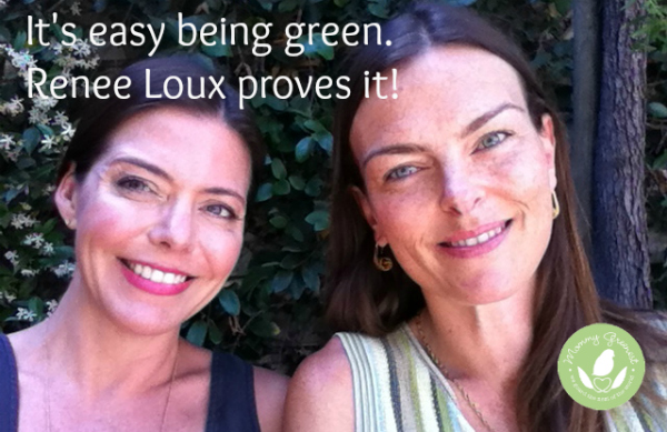 two smiling brunette women against a wall of green leaves