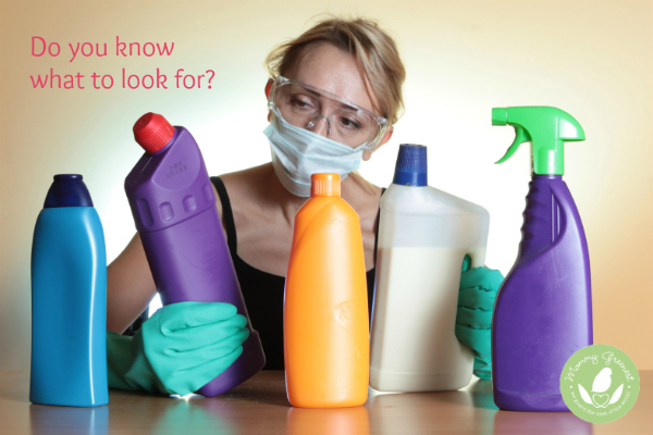 woman wearing breathing mask and gloves inspects several unlabeled cleaning product bottles.
