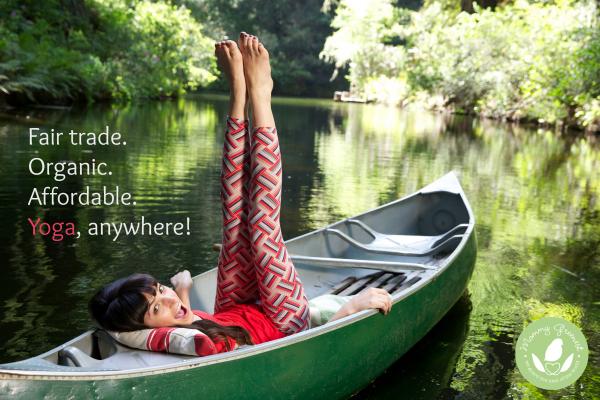 brunette model wearing red patterned hot yoga pants in rowboat on glassy forest lake