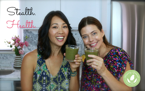 two women hold glasses of green smoothie juice