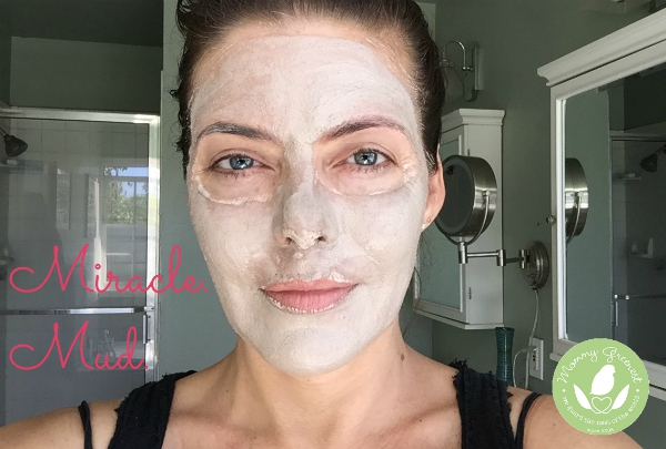brunette woman in bathroom with mud natural face mask on her face