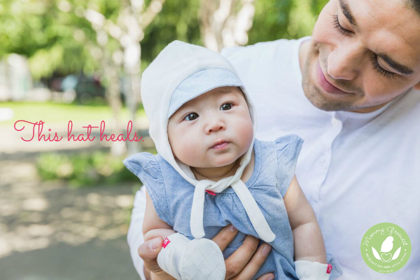asian baby held by dad wearing eczema healing hat and gloves