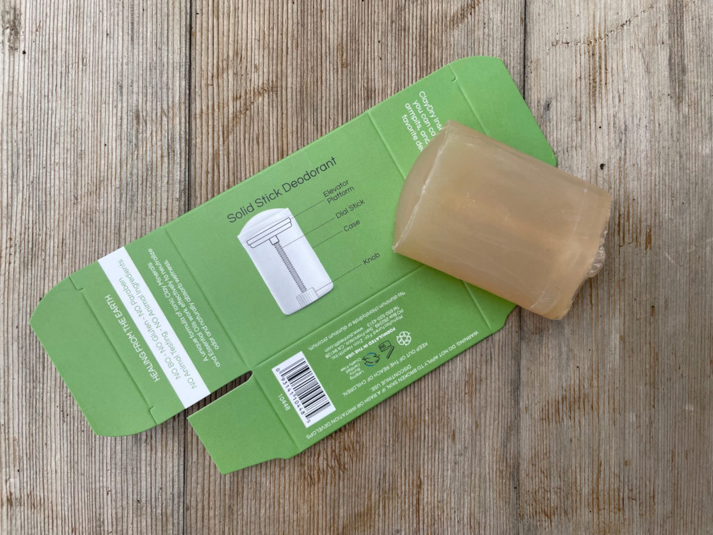 Refillable zero waste natural deodorant stick on paper packaging set on a wood table outside.